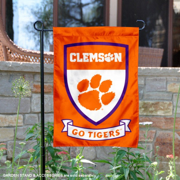 Clemson Go Tigers Shield Garden Flag is 13x18 inches in size, is made of thick blockout polyester, screen printed university athletic logos and lettering, and is readable and viewable correctly on both sides. Available same day shipping, our Clemson Go Tigers Shield Garden Flag is officially licensed and approved by the university and the NCAA.