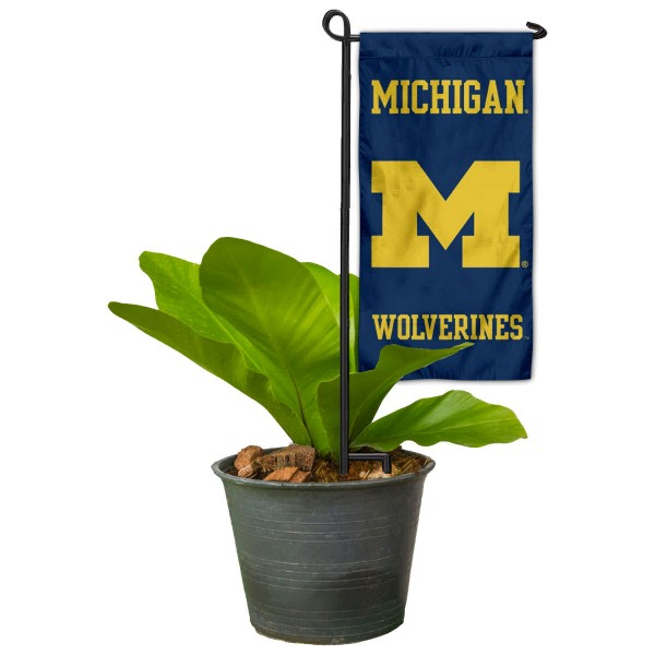 """Michigan Wolverines Flower Pot Topper Flag kit includes our 4""""x8"""" mini garden banner and 6"""" x 14"""" mini garden banner stand. The mini flag is made of 1-ply polyester, has screen printed logos and the garden stand is made of steel and powder coated black. This kit is NCAA Officially Licensed by the selected college or university."""